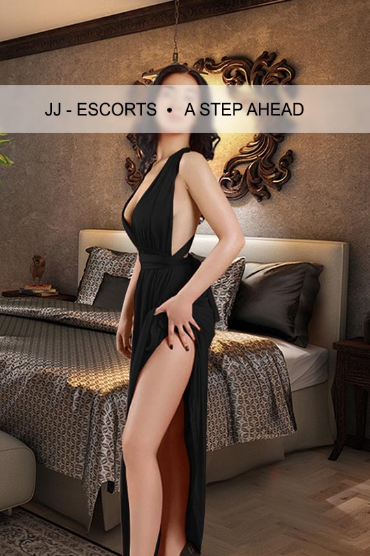 Escort Damen Asa Kim mit schwarzem Kleid am Bett