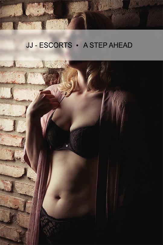 Escort Damen Emily Blurr an einer Wand stehend mit schwazen Dessous